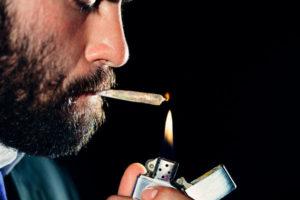 Man lighting and smoking a marijuana joint